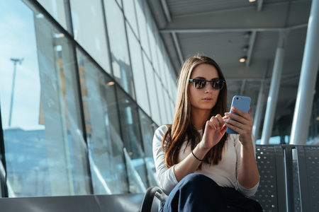 Young beautiful woman sitting at the airport terminal departure lounge and using smartphone while waiting for a flight. Travel concept. Travel passenger girl browsing internet on mobile phone. Imagens