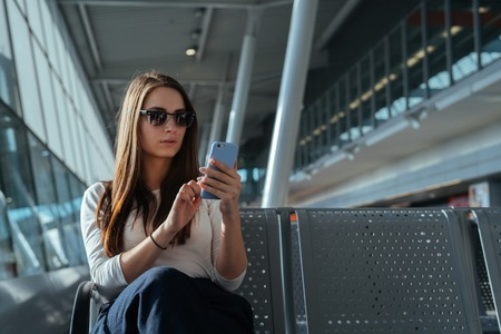 Young woman in sunglasses sitting at the gate and using smartphone while waiting for a flight at the airport. Travel concept. Passenger girl chatting in terminal departure lounge.