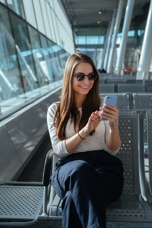 Young smiling woman in sunglasses sitting at the gate and using smartphone while waiting for a flight at the airport. Travel concept. Girl chatting in terminal departure lounge. Imagens