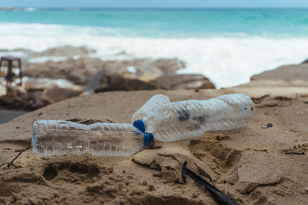 Plastic water bottles on the beach left by tourists. Pollution in ocean. Environment concept Imagens