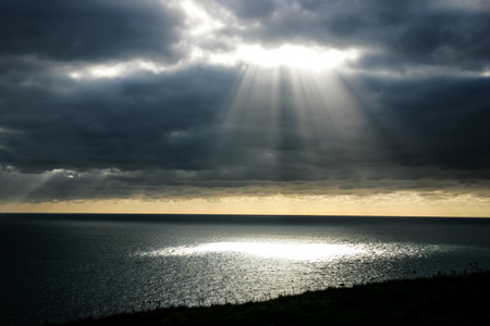 shafts: A shaft of light breaking through the dark clouds.  Provides imagery of hope, faith, religion