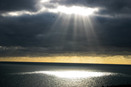 A shaft of light breaking through the dark clouds.  Provides imagery of hope, faith, religion