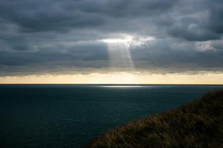 breaking through: A shaft of light breaking through the dark clouds.  Provides imagery of hope, faith, religion