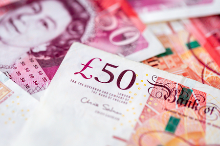 Bitcoin with a pile of fifty pound sterling bank notes Stock Photo