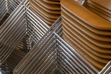 Stacked chairs with wooden seats and metallic legs Фото со стока