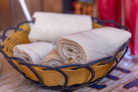 Rolls of Injera in a serving bowl.  Injera is a sourdough flatbread made from teff flour.  It is the national dish of Ethiopia, Eritrea, Somalia and Djibouti Reklamní fotografie