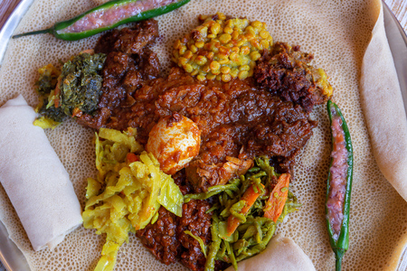 Injera served with Chicken and egg Doro Wat, berbere, vegetables and lentils.  Injera, the national dish of Ethiopia, is a sourdough flatbread made from teff flour. Imagens