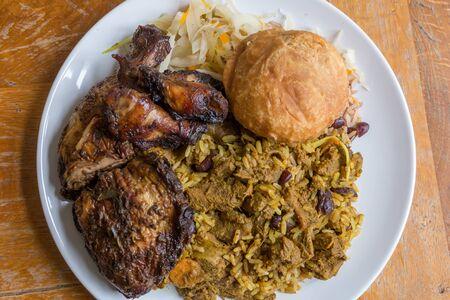 Chèvre au curry jamaïcain traditionnel, poulet jerk et boulette frite avec riz et petits pois