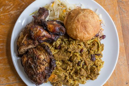 Traditional Jamaican curried goat, jerk chicken and fried dumpling with rice and peas