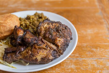 Traditional Jamaican curried goat, jerk chicken and fried dumpling with rice and peas Banque d'images