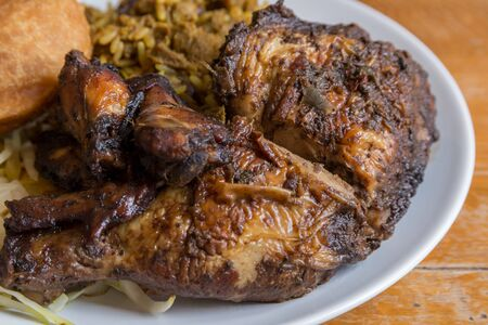 Traditional Jamaican curried goat, jerk chicken and fried dumpling with rice and peas Stock Photo