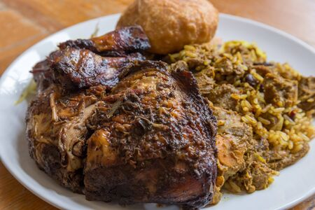 Traditional Jamaican curried goat, jerk chicken and fried dumpling with rice and peas 스톡 콘텐츠