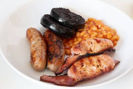 Cumberland sausages, back bacon, baked beans and black pudding in a white bowl