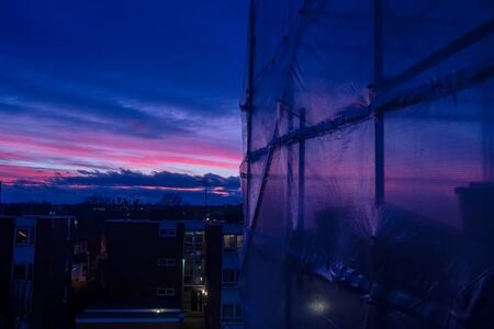 Scaffolding and protective cover sheets on a residential building at sunset 写真素材