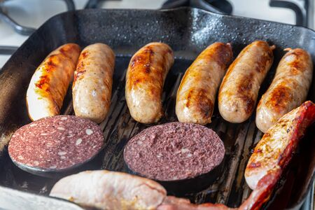 Cumberland sausages, back bacon and black pudding cooking in a griddle pan 版權商用圖片
