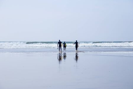 Surfers, carrying surfboards, walking into the water in Cornwall, UK