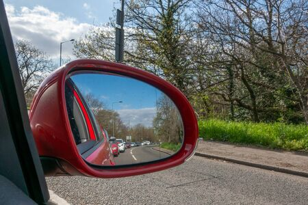 Heavy London traffic viewed in the reflection of a car wing mirror