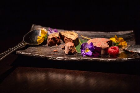 Indulgent, stylish chocolate based dessert decorated with colourful flowers. With copy space
