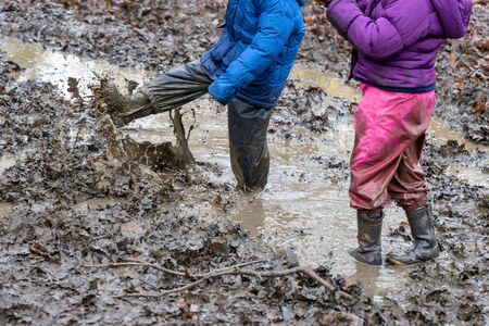 Young children playing in a muddy puddle Stock Photo