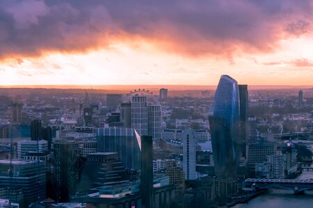 Hazy, menacing sky above London cityscape at sunset with a dystopian feel