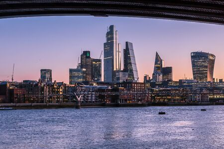 Sunrise view of London skyline and skyscrapers, from across the River Thames, framed by Blackfriars Bridge