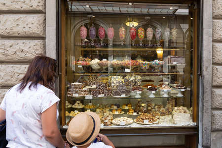 Florence, Italy - August 13 2019: Mother and child admiring the window display at Migone sweet and candy shop in Florence
