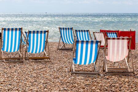 Chaises longues à rayures colorées à louer sur la plage de galets à Brighton, East Sussex, Angleterre