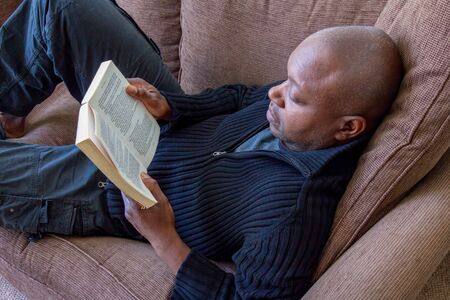 Black man, of African ethnicity, reading on the sofa