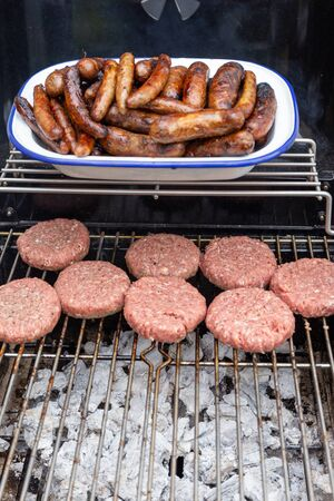 Burgers and sausages on an outdoor garden barbecue