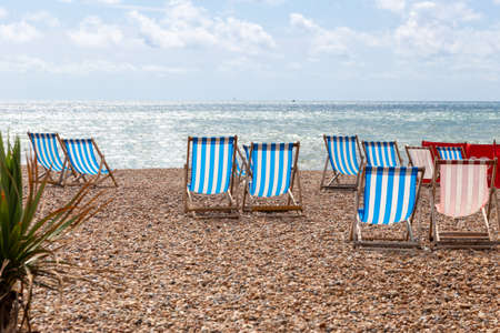 Colourful striped empty deck chairs for rent on the pebble beach at Brighton, East Sussex, England
