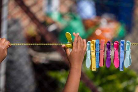 A young african american child playing with clothes pegs and a washing line in the garden