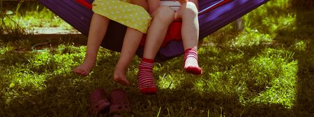 girl sitting in a hammock, legs dangling . summer childhood vacation Stock Photo