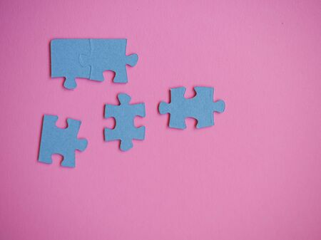 several pieces of the puzzle lie on a solid background Imagens