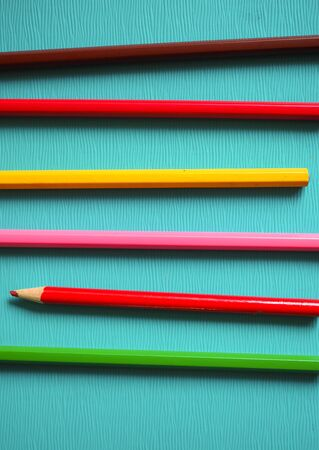 bright colored pencils lie on a blue background office creativity