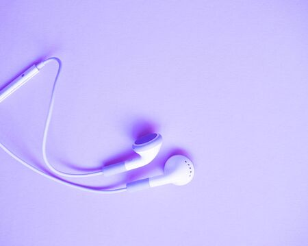 simple white headphones lie on a light background