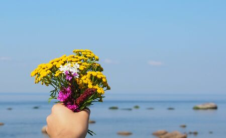 girl holding a bouquet of yellow wildflowers close-up