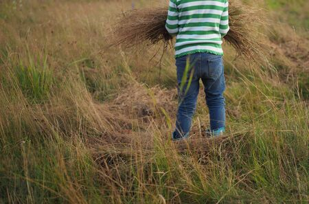 a child plays in a field with hay