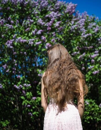 beautiful girl model stands back against the background of a Bush with flowers Imagens