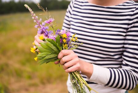 young beautiful girl holding a bouquet of wild flowers Stock Photo