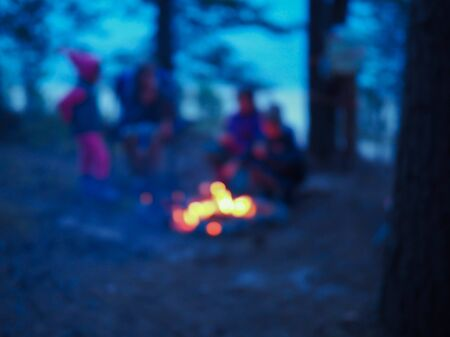 people and children sit around the campfire at night blurred view Stock Photo