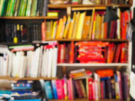 blurry image of a shelf with lots of brightly colored books Stock fotó
