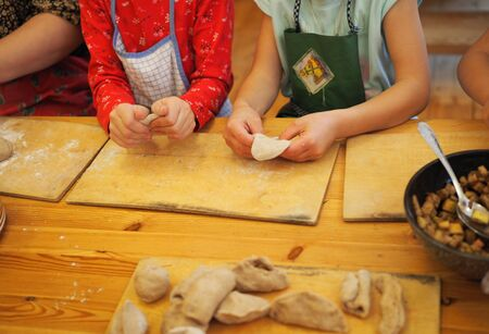 children work together to roll out dough for baking Stock Photo