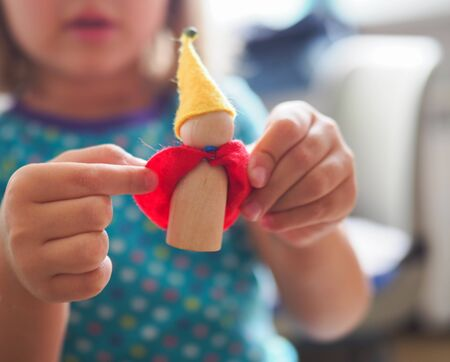 a child is holding a toy wooden gnome Stock Photo