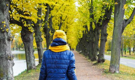 a girl in a jacket and hat walks along the autumn alley Stock Photo