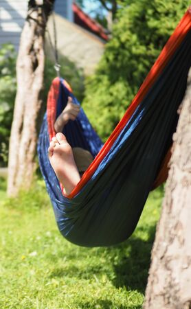 girl resting lying in a hammock in the summer garden