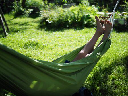 girl resting lying in a hammock in the summer garden