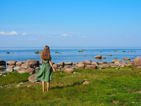 young beautiful girl happy in the background of the sea rear view Stockfoto