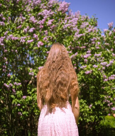 beautiful girl model stands back against the background of a Bush with flowers Stockfoto