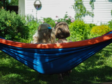 two little girls sitting in hammock in summer in garden rear view