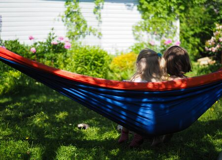 two little girls sitting in hammock in summer in garden rear view Stock fotó - 133569814